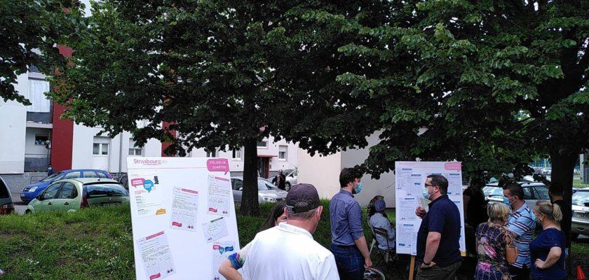 Plusieurs personnes discutant autour de panneaux informatifs